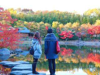 池の前に立っている人の写真・画像素材[881138]