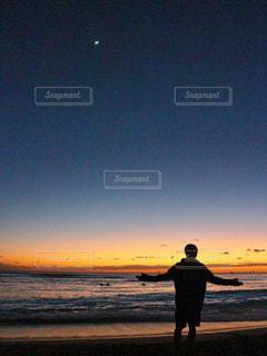 日没の前にビーチに立っている人 - No.978472