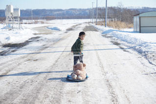 雪の中で立っている少年の写真・画像素材[1686856]