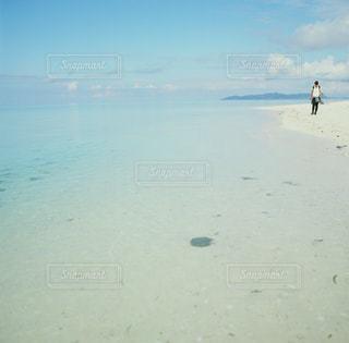 海の横にある砂浜に立っている人の写真・画像素材[713378]