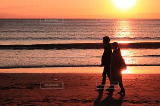 バック グラウンドで夕焼けのビーチに立っている人の写真・画像素材[977966]