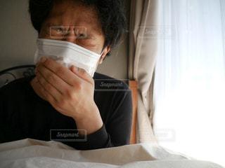 ベッドの上で咳込む男性の写真・画像素材[1063771]