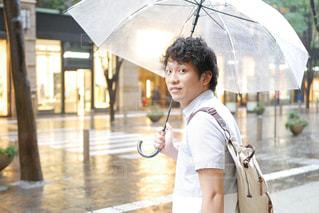 傘を持って雨の中で立っている少年の写真・画像素材[1263871]