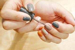 マニキュアを持ち、爪を塗っている女性の手の写真・画像素材[1568306]