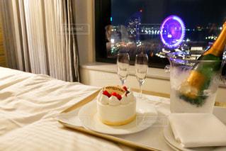 テーブルの上に食べ物のプレートが付いているベッドの写真・画像素材[1668556]