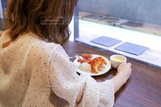 食卓に座って食べ物を食べる1人の女性の写真・画像素材[2130120]