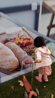食べ物,ピンク,後ろ姿,散歩,子供,女の子,パン,人物,背中,人,後姿,幼児,小人,子育て,トリック写真,キックボード,色・表現