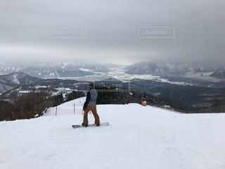 煙る山頂の雪をスノーボードに乗る男 - No.929317