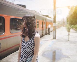 電車の横に立っている女性 - No.934339