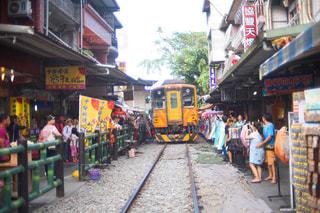 電車の横の通りを歩く人々 のグループの写真・画像素材[952368]