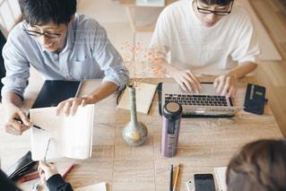 ノート パソコンを見てテーブルに座っている人々 のグループの写真・画像素材[1322710]