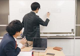ホワイトボードにグラフを書いて説明するビジネスマンの写真・画像素材[1667819]