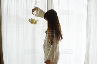 カーテンの前に立っている女性の写真・画像素材[2168649]