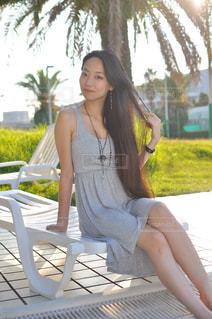 カメラにポーズのベンチに座っている女性 - No.877534