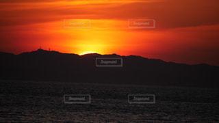 海の向こうの山に沈む夕陽の写真・画像素材[2863682]