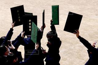 中学校の校庭で卒業証書を掲げて歓声を上げる中学生の写真・画像素材[4270415]