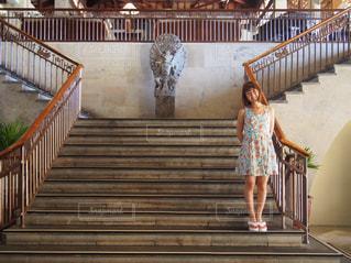木製のフェンスの横に立っている女の子の写真・画像素材[1016997]