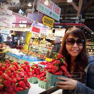 果物の屋台の前に立っている女性の写真・画像素材[1025576]