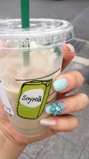 プラスチック製のカップを持っている手の写真・画像素材[1169544]