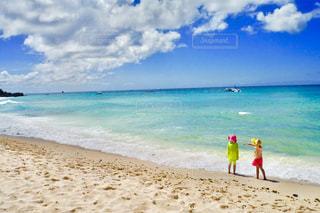 海の横にある砂浜のビーチの上に立っている人の写真・画像素材[1181109]