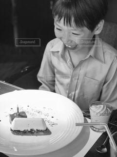 プレートの前のテーブルに座っている少年の写真・画像素材[1185504]