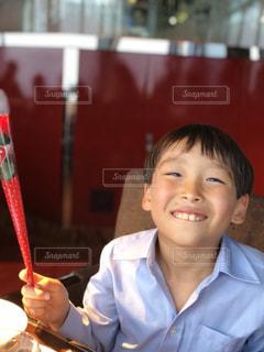 テーブルに座って、カメラで笑顔の少年の写真・画像素材[1261540]