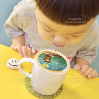一杯のコーヒーをテーブルに座って男の子の写真・画像素材[1467130]