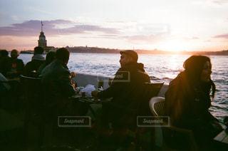 水の体の横に立っている人のグループの写真・画像素材[1232744]