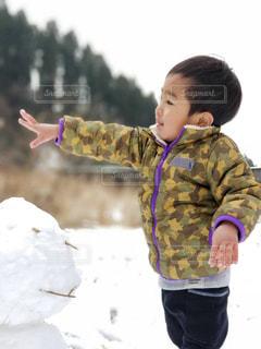 雪の中で立っている少年の写真・画像素材[1000829]