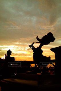 日没の前に立っている人々 のグループの写真・画像素材[956940]
