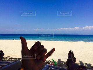 水の体の近くのビーチに座っている男 - No.741336