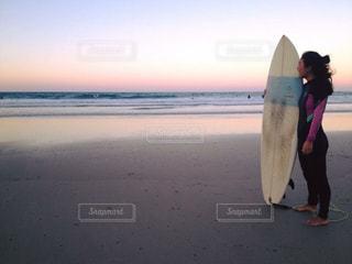 ビーチの上を歩くサーフボードを運ぶウェット スーツの人 - No.963083