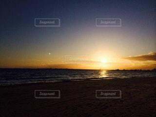 海の横にあるビーチに沈む夕日 - No.963090