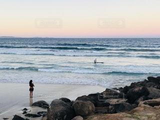 海の横にある岩のビーチに立っている人 - No.963331
