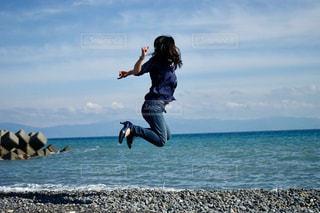 海の横にある岩のビーチで空気を通って飛んで男の写真・画像素材[1261051]