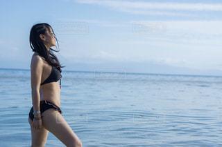 水の体の横に立っている女性の写真・画像素材[1385156]