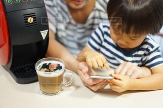一杯のコーヒーをテーブルに座っている少年の写真・画像素材[1467771]