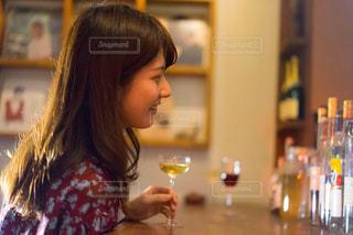 ワイングラスを持つテーブルに座っている女性の写真・画像素材[1634433]