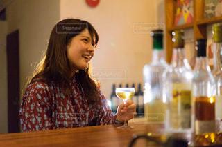 テーブルの上にワインのボトルを保持している女性の写真・画像素材[1634438]
