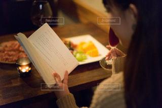 テーブルの上のワイングラスを持っている人の写真・画像素材[1634474]