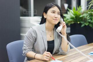 ラップトップを使用してテーブルに座っている女性の写真・画像素材[1680069]