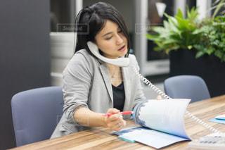 ラップトップを使用してテーブルに座っている女性の写真・画像素材[1680072]