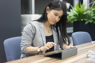ラップトップを使用してテーブルに座っている女性の写真・画像素材[1680578]