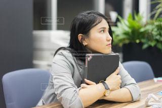 ラップトップを使用してテーブルに座っている女性の写真・画像素材[1680581]