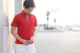 赤いシャツを持った男の写真・画像素材[2171952]