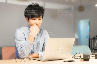 テーブルの上に座っているラップトップコンピュータを使う少年の写真・画像素材[2342653]