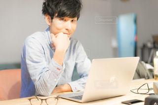 テーブルの上に座っているラップトップコンピュータを使う少年の写真・画像素材[2342657]