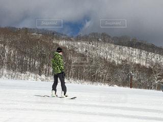 雪に覆われた斜面をスノーボードに乗っている男の写真・画像素材[2944124]