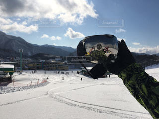 雪に覆われた山をスノーボードに乗っている人の写真・画像素材[2944126]