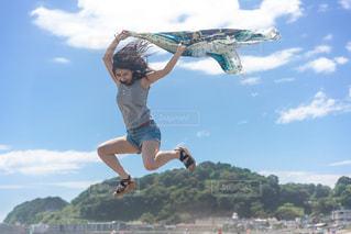 スケートボードに乗っている間に空を飛んでいる男の写真・画像素材[2980098]